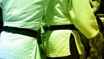 2 judoka fighting representing defensiveness, one of the 4 toxins of teamwork