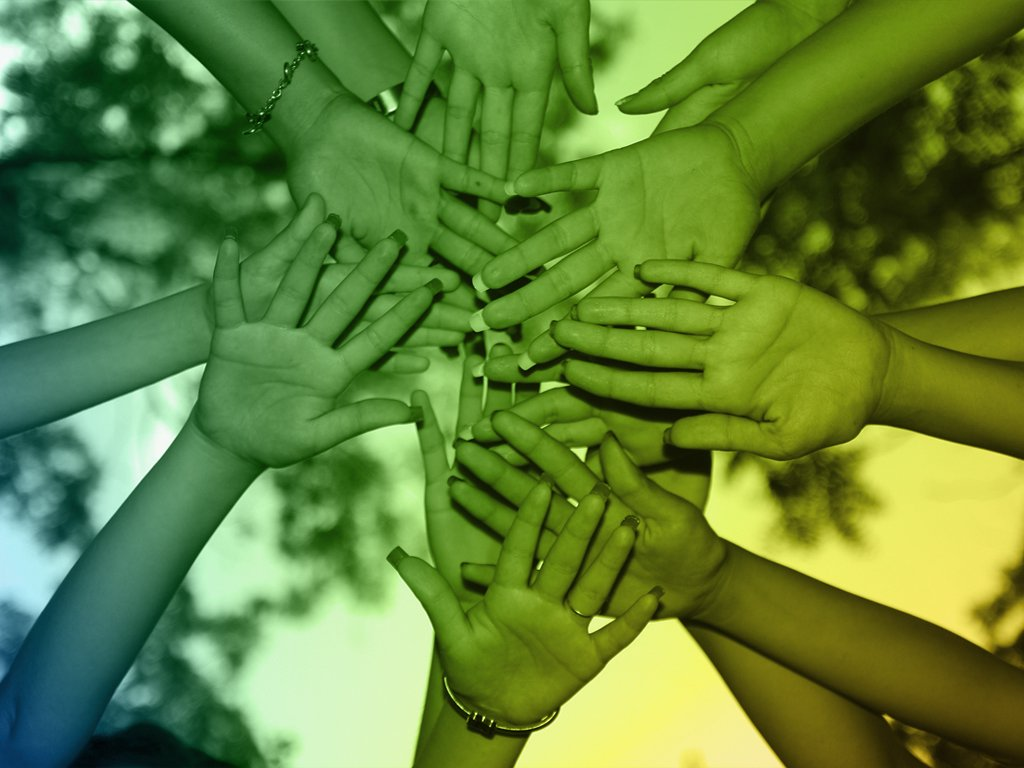 Team members join their hands during a team coaching or team building activity
