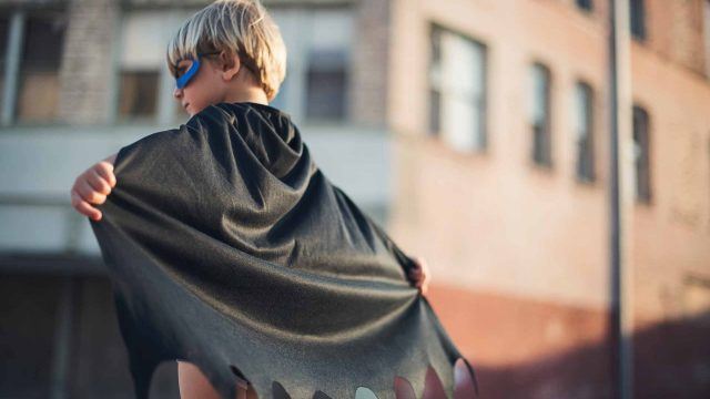 A child with a superhero cape representing 4 leadership qualities of an effective leader